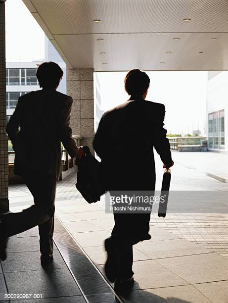 Businessmen with briefcase running, rear view