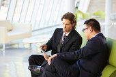 Businessmen With Digital Tablet Sitting In Modern Office