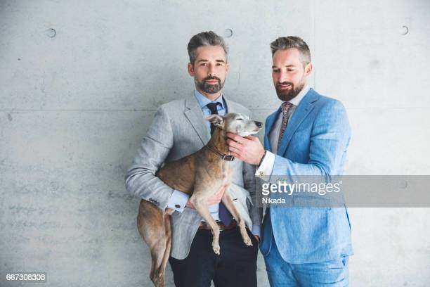 Businessmen with dog against gray wall