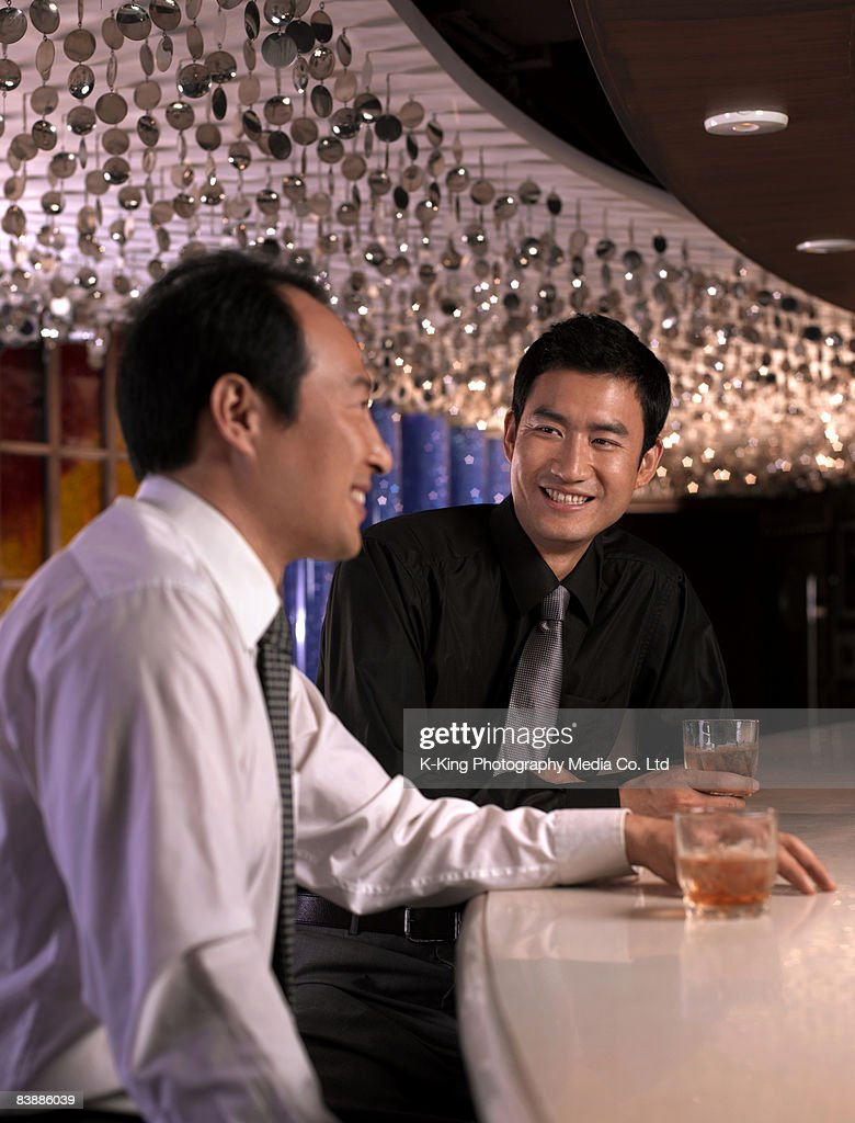 Businessmen with drinks at bar. : Stock Photo