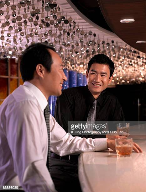 Businessmen with drinks at bar.