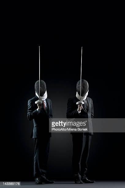 Businessmen with fencing masks holding up fencing foils