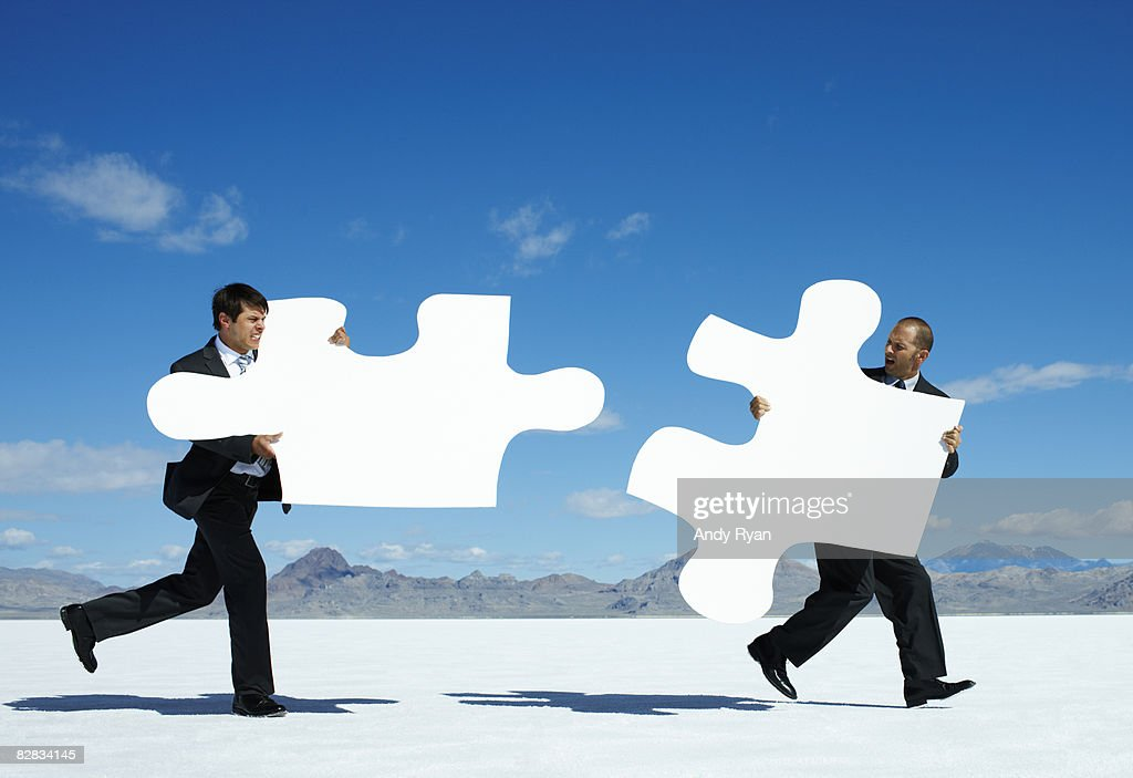 Businessmen with Giant Puzzle Pieces Running. : Stock Photo