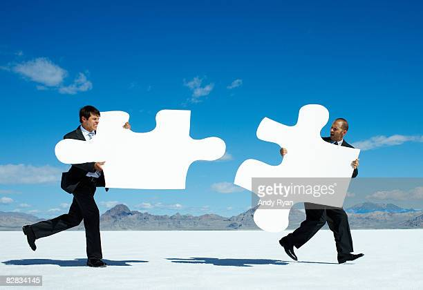 Businessmen with Giant Puzzle Pieces Running.