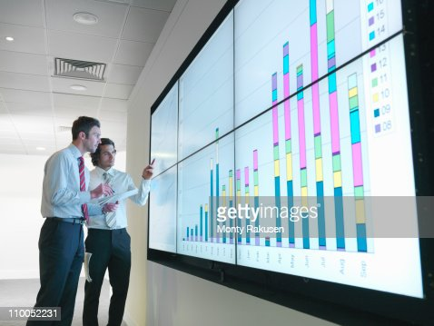 Businessmen with graphs on screen : Stock Photo