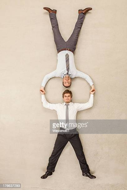 Businessmen with head to head position and holding hands against beige background