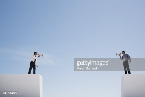 Businessmen with megaphones on walls with gap shouting : Stock Photo