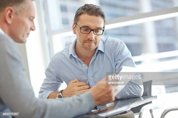 Businessmen with tablet during meeting