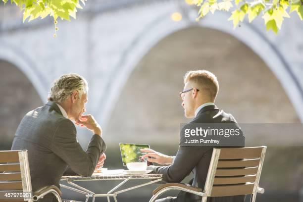Businessmen working at sidewalk cafe