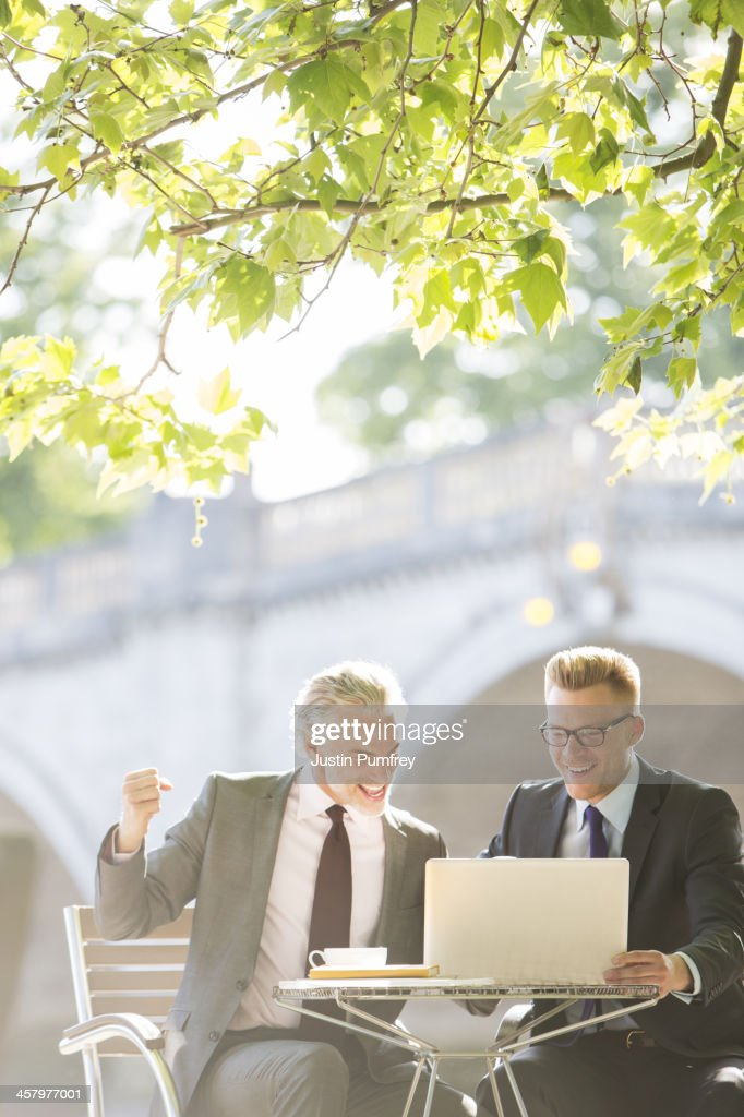 Businessmen working at sidewalk cafe : Stock Photo