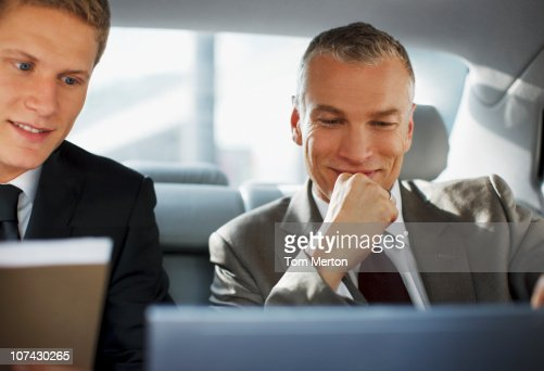 Businessmen working in back seat of car : Stock Photo