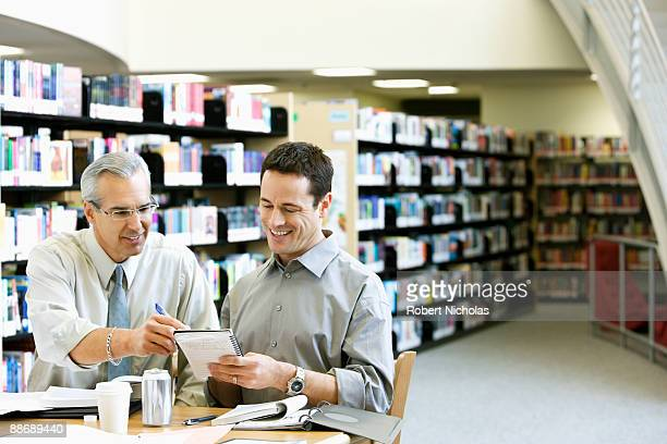 Businessmen working in library
