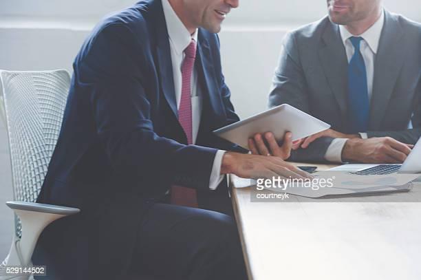 Businessmen working together on a digital tablet.