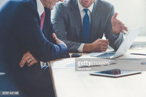 Hommes d'affaires travaillant ensemble sur un ordinateur portable.