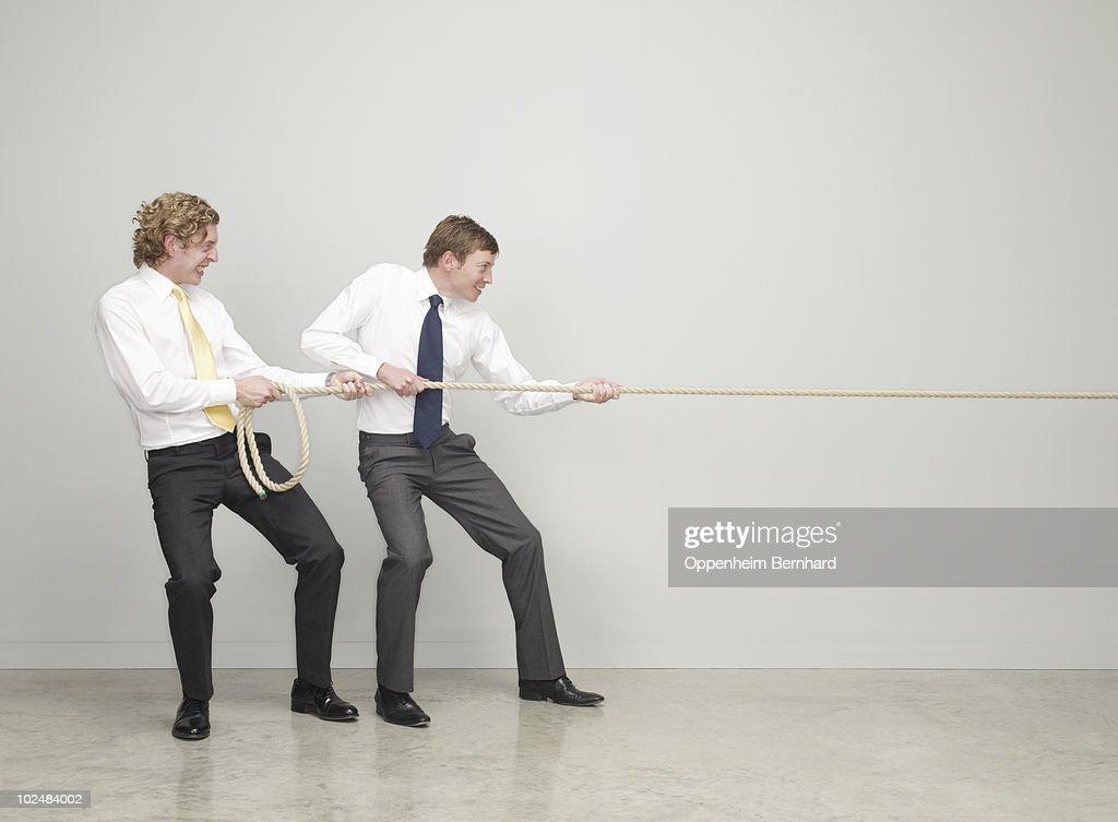 businessmen working together pulling rope