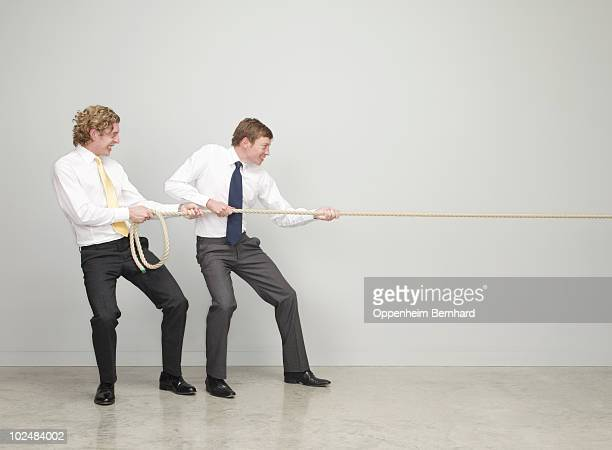 businessmen working together pulling rope