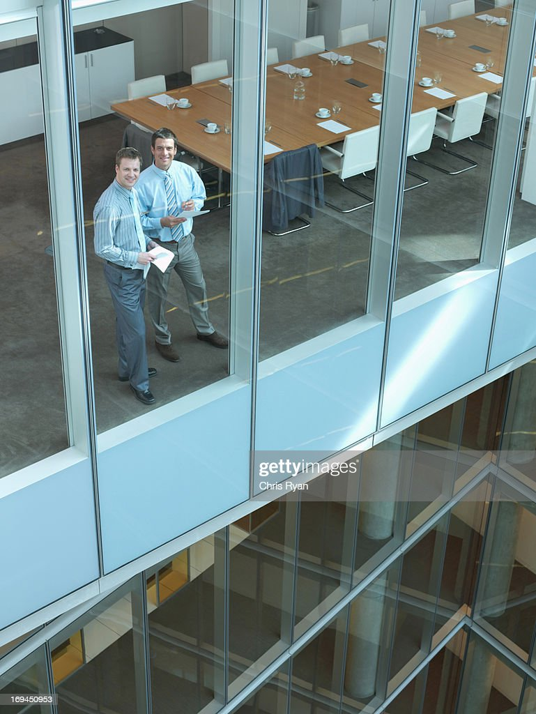 Businessmens standing in conference room with paperwork : Foto stock