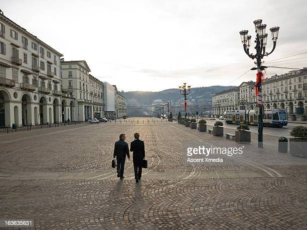 Businessmens walking across piazza at sunrise
