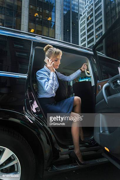 Businessowman on phone getting out of car