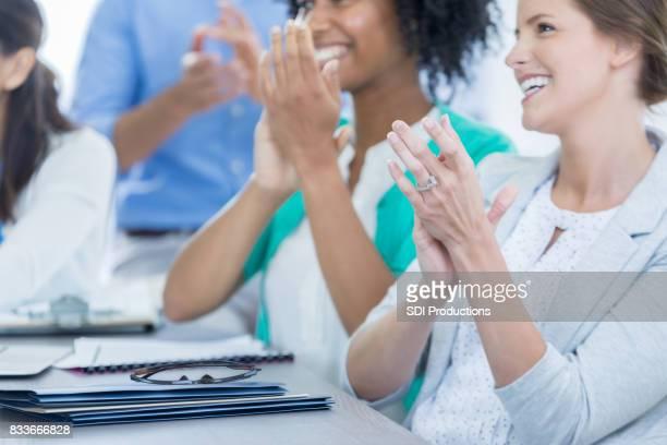 Businesspeople applaud colleague after presentation