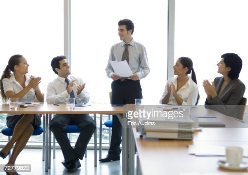 Businesspeople applauding colleague in conference room