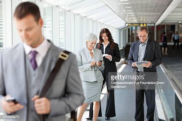 Businesspeople at airport using conveyor belt