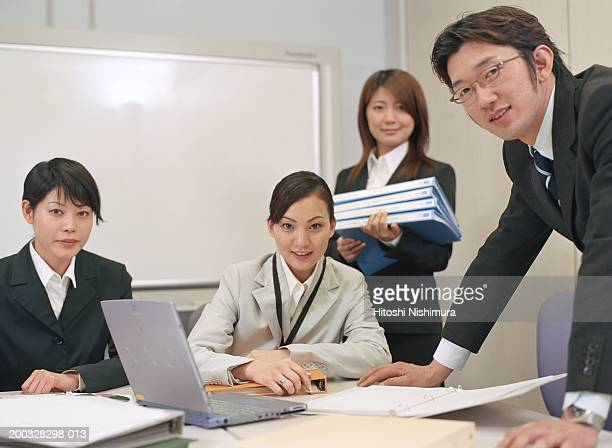 Businesspeople at conference table, smiling, portrait