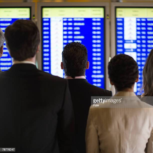 Businesspeople at the Airport Looking at Departure Monitor