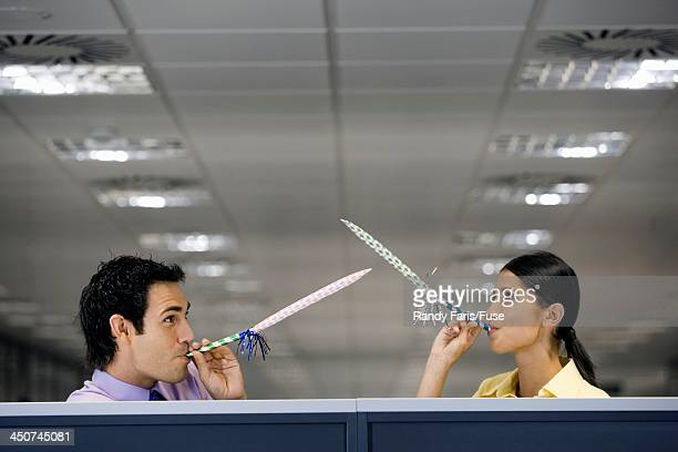 Businesspeople Blowing Into Party Favors
