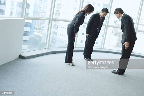 Businesspeople bowing at one another