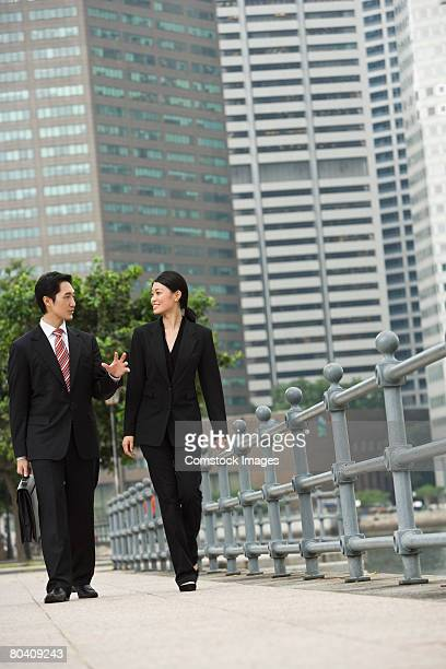 Businesspeople chatting while walking