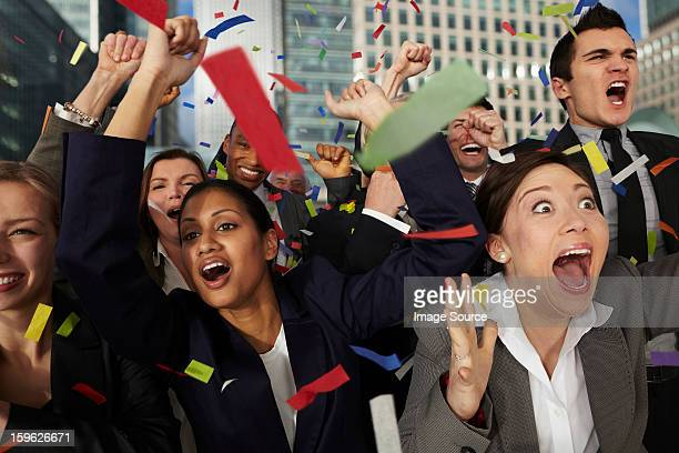 Businesspeople cheering as ticker tape falls