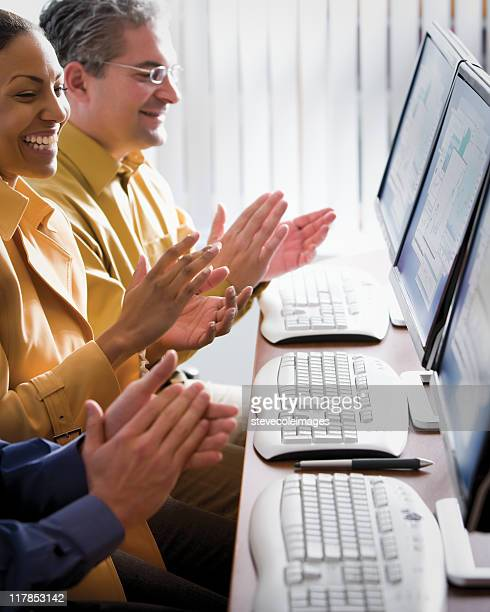 Businesspeople Clapping at Reports on Monitors