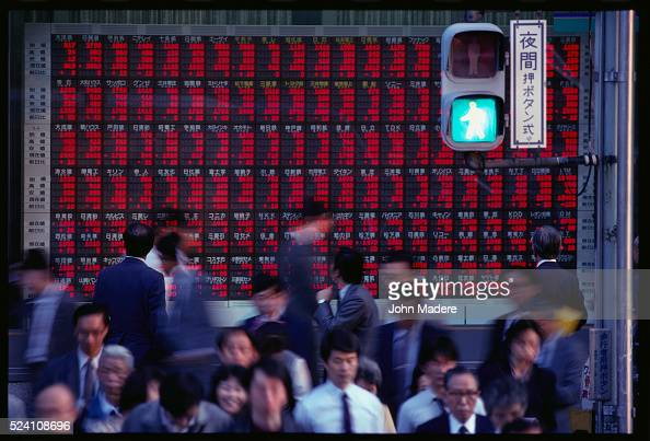 Businesspeople cross the street as they check the Tokyo stock market prices on display