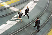 Businesspeople crossing train tracks