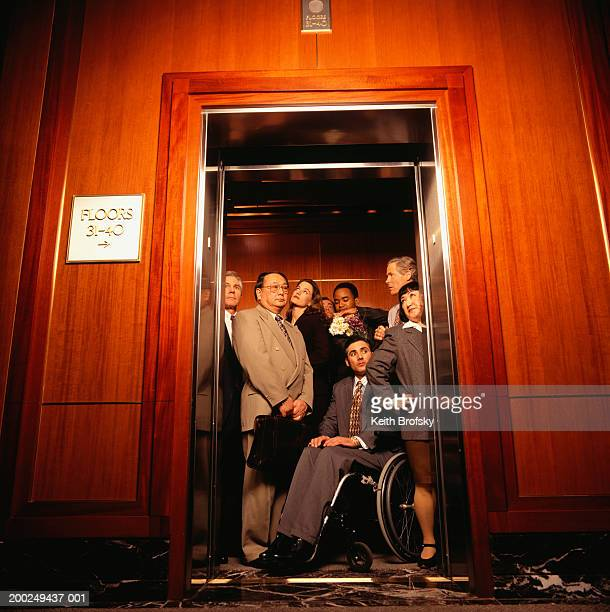 Businesspeople crowded in elevator, one man in wheelchair