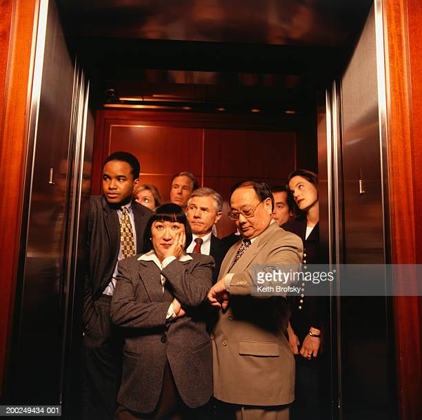 Businesspeople crowded in elevator, waiting