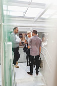 Businesspeople discussing on steps in modern office