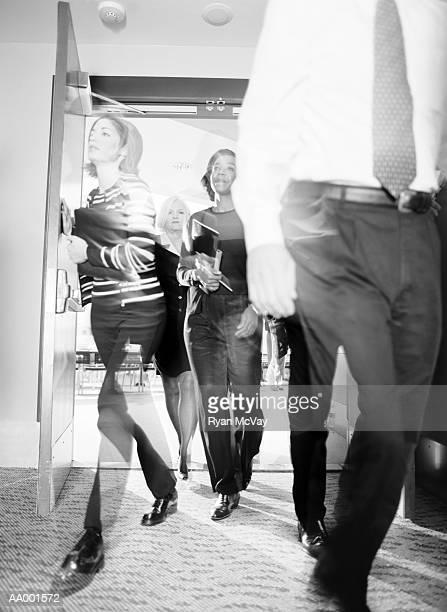 Businesspeople Exiting Through an Open Doorway