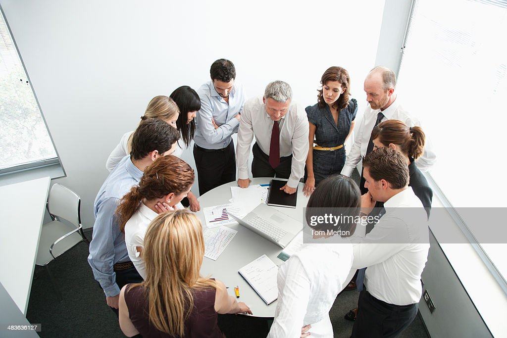Businesspeople gathering around office table : Stock Photo