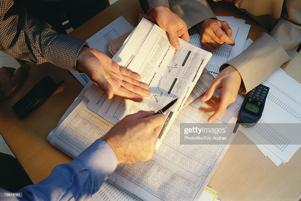 Businesspeople gesturing across table to financial pages of newspaper, cropped view