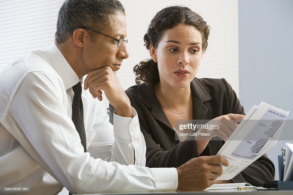 Businesspeople going over report : Stock Photo