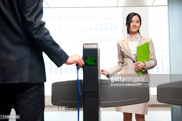 Businesspeople going through security turnstile, Tokyo Prefecture, Honshu, Japan