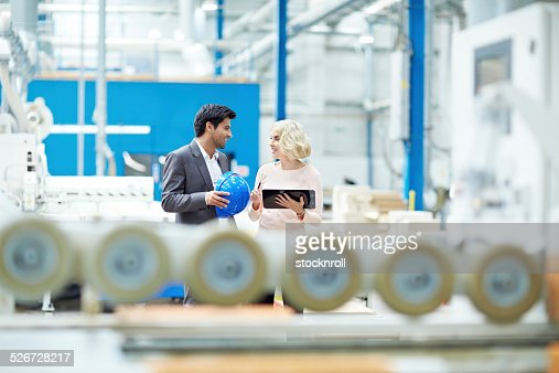 Businesspeople having a conversation at factory shopfloor