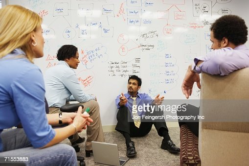 Businesspeople having a meeting in front of a whiteboard wall