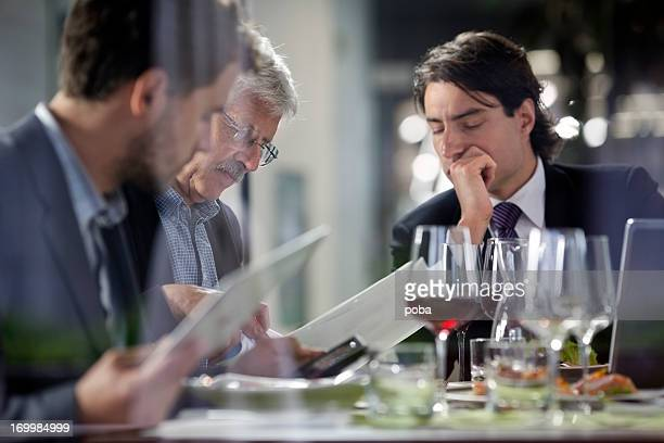 Businesspeople having lunch at restaurant and  studying paperwork