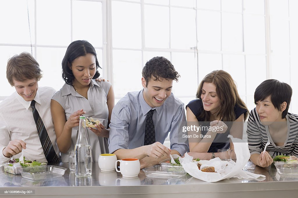 Businesspeople having lunch in office : Stock Photo