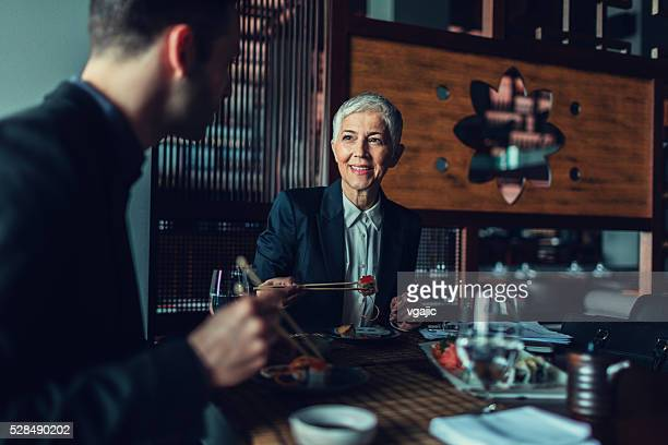 Businesspeople Having Meeting and Lunch In A Restaurant.