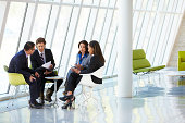 Four Businesspeople Having Meeting In Modern Office Reception Area