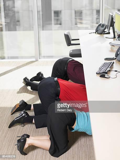 Hommes d'affaires se cachent sous bureau de travail